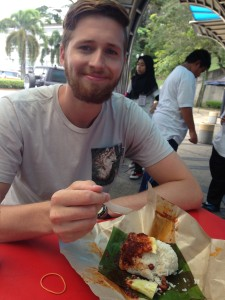 Alex eating some nasi lemak bungkus (coconut rice with sambal chili that is wrapped with banana leaf).  A yummy street food meal that cost 2 Malaysian Ringets (50 cents).