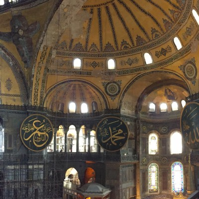 The inside of Hagia Sophia.  In the photo you can see gigantic circular-framed disks or medallions were hung on columns. These were inscribed with the names of Allah, Muhammad, among others.