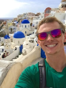 "Me with the famous three domes in the town of Oia.  The small town is known for its sunsets, luxury boutique hotels, and quaint Atlantis bookstore (which was an unlikely recipient of one of ""The world's ten best bookstore awards"" recently."