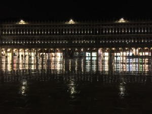 The plaza of San Marco at night reflecting the light off the wet ground.